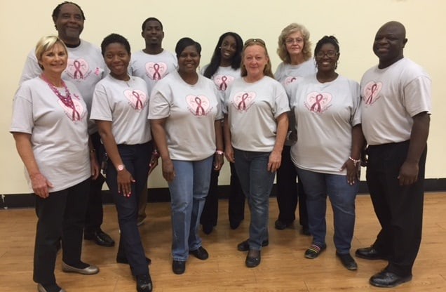 Staff members of Nova Academy pose in their Breast Cancer Awareness T-shirts designed by teacher Sade Burkman and her students.